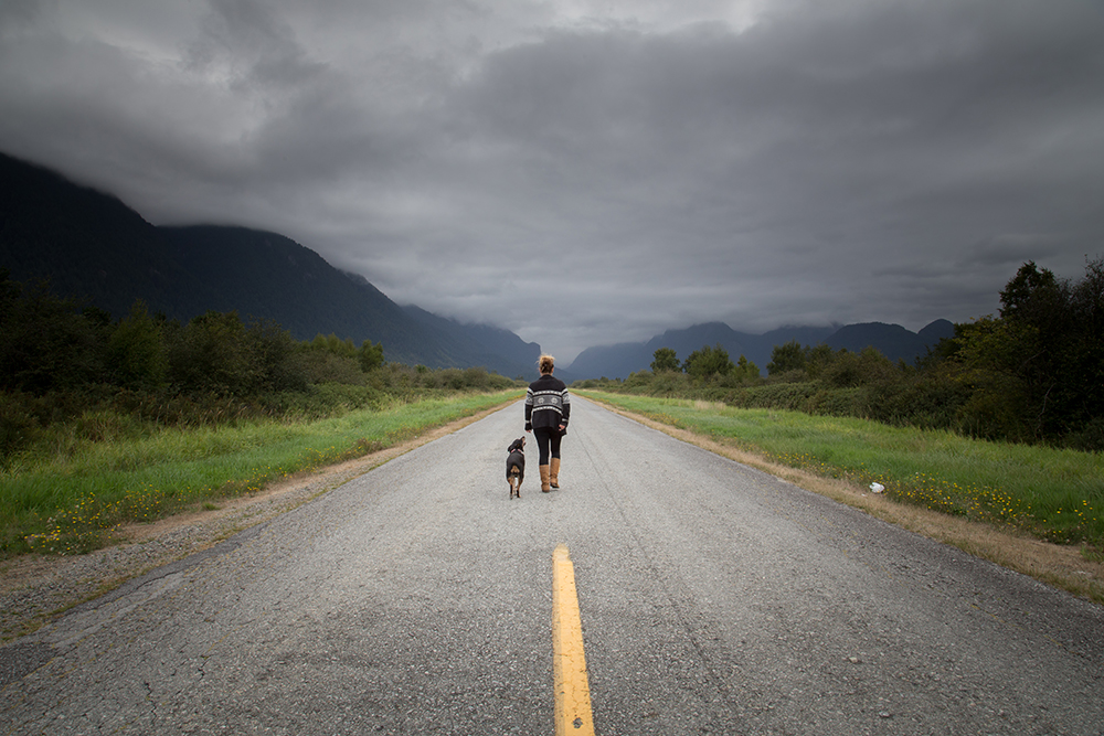 A girl walking down the middle of a road with a dog beside her
